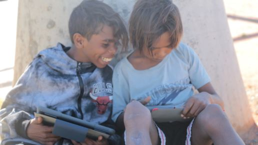 Two smiling Aboriginal boys looking at iPads.